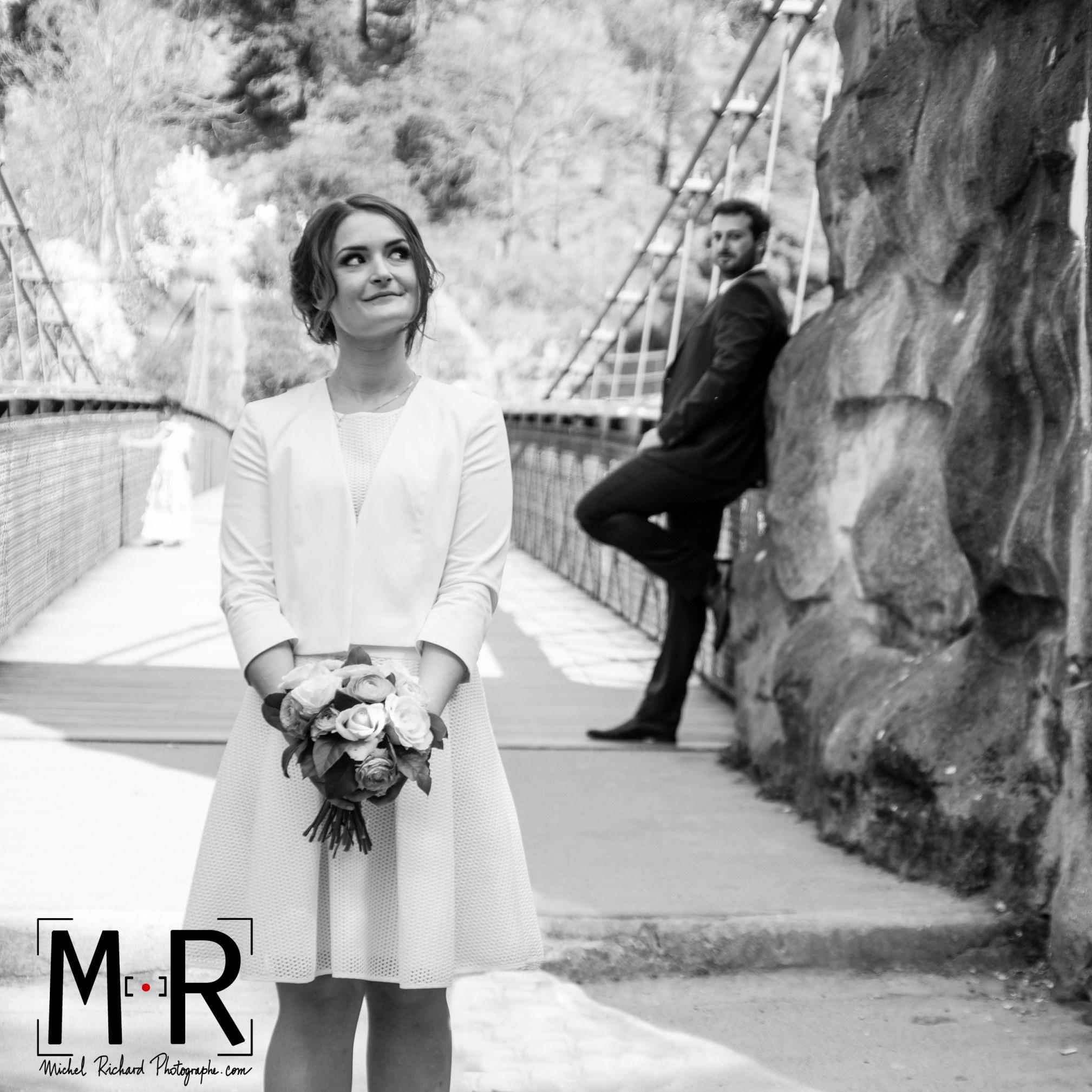 Le marié regarde la mariée de loin. La mariée a un air coquin et regarde en l'air.
