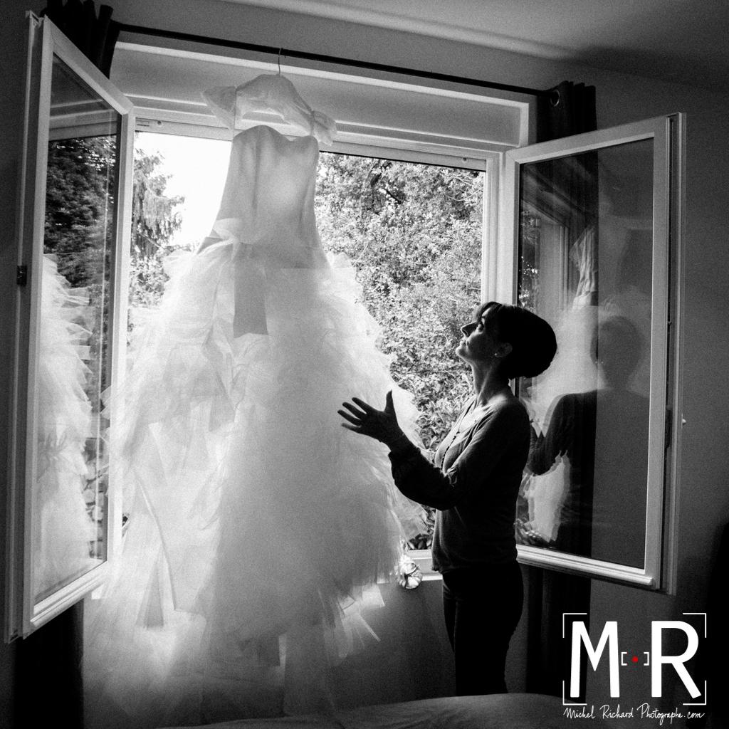 Mariage-preparatifs-La mariée regarde sa robe à la fenêtre-Michel-Richard