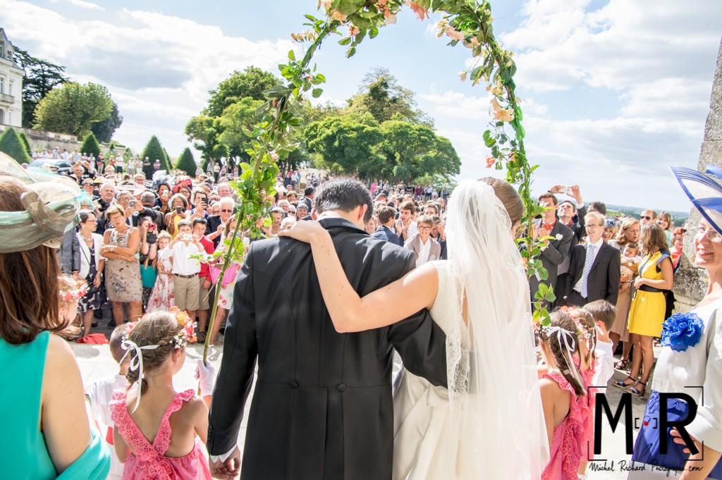 les mariés de dos face à la foule à la sortie de l'église après la messe pour leur cérémonie de mariage