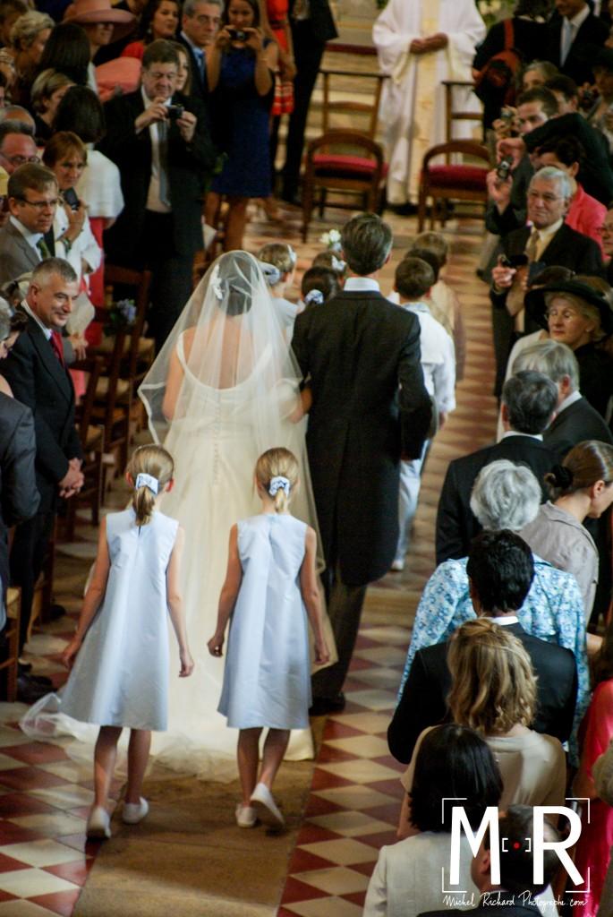 la mariée de dos aux bras de son père avance avec le cortège des enfants d'honneur. Belle lumière sur le voile et les robes. cérémonie de la messe de mariage.