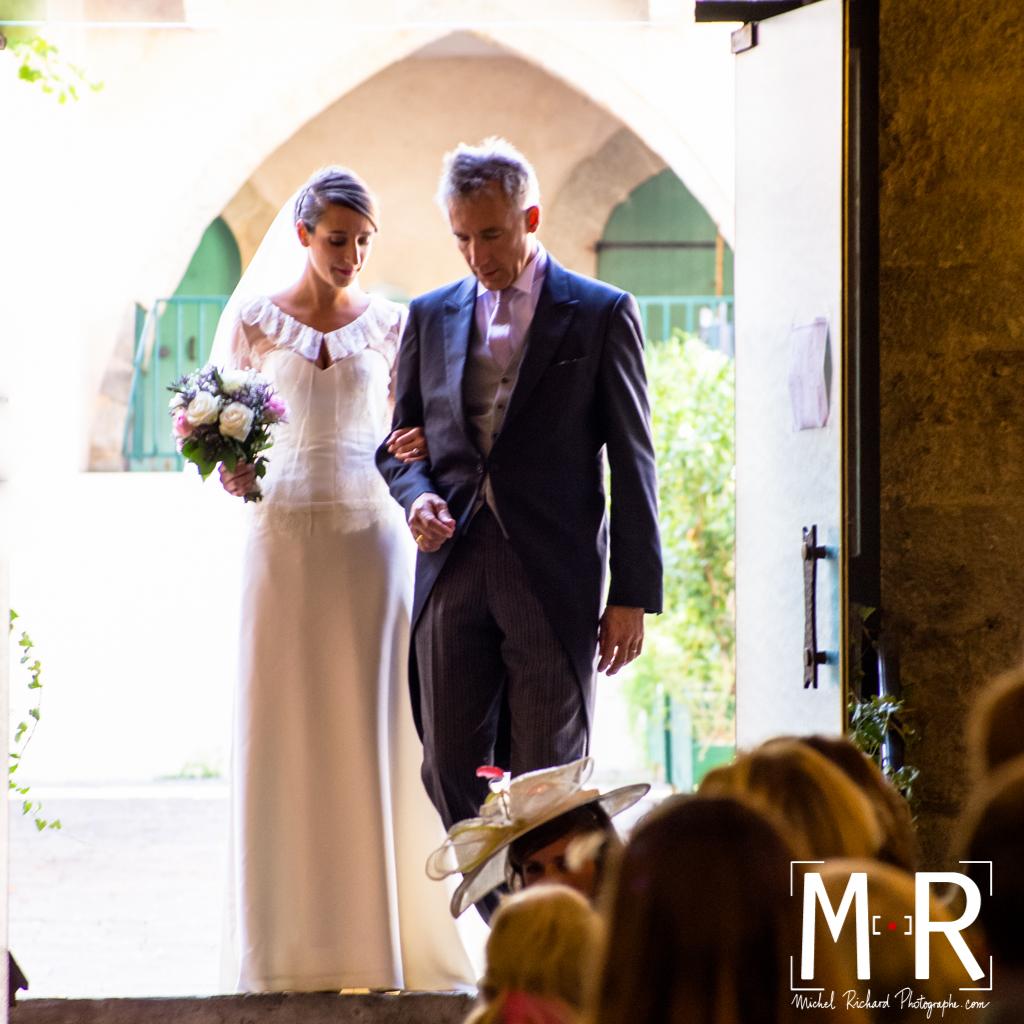 la mariée rentre aux bras de son père dans l'église sous une belle lumière et un bel éclairage sur les visages. cérémonie de la messe de mariage.