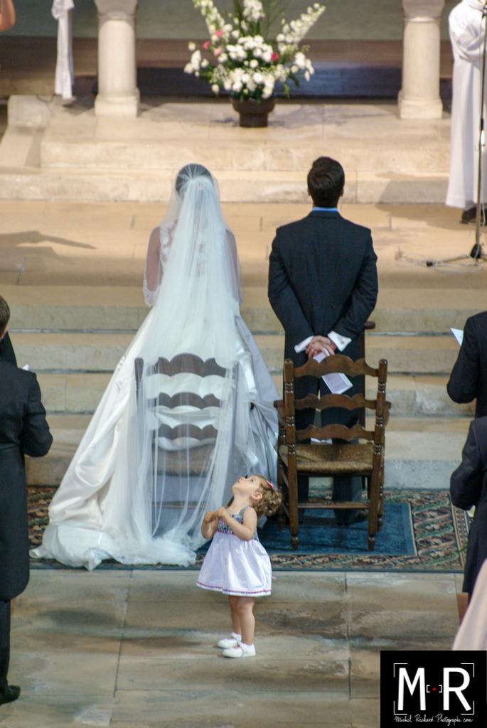 un enfant - une petite fille d'honneur regarde en l'air derrière les mariés à l'église pendant la cérémonie de la messe du mariage