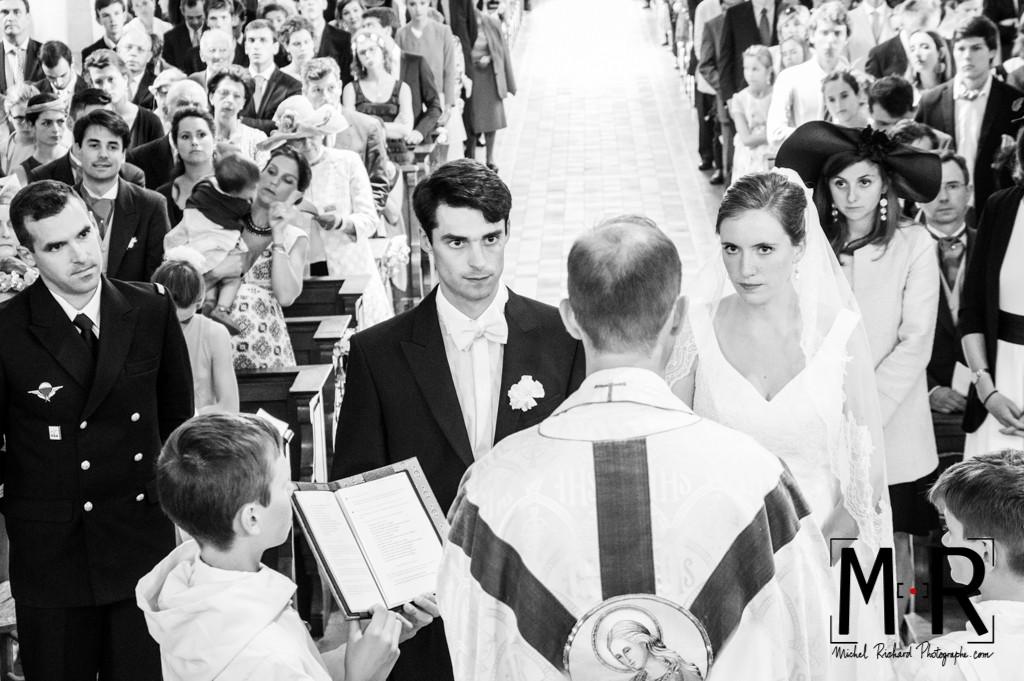 les mariés regardent le prêtre pendant l'échange des consentement et la bénédiction à l'église, pour la cérémonie du mariage, la messe.