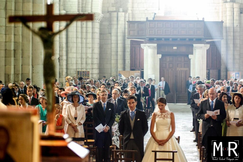 les mariés en prière devant la croix sur l'autel de l'église pour la cérémonie de mariage. Un rayon de soleil illumine les têtes pendant la messe de mariage.