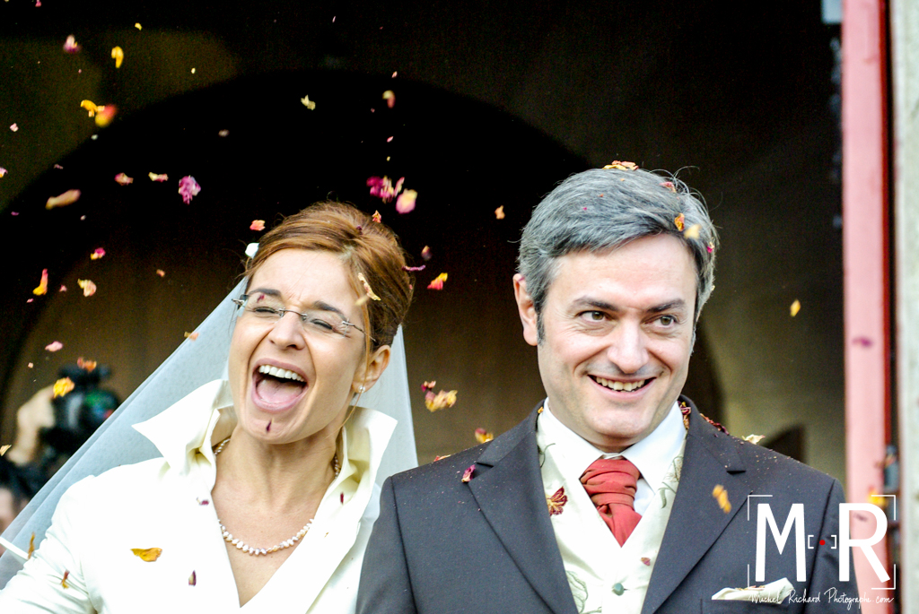 les mariés rient à la sortie de la messe sous la pluie de pétales de roses après la cérémonie religieuse du mariage à l'église.