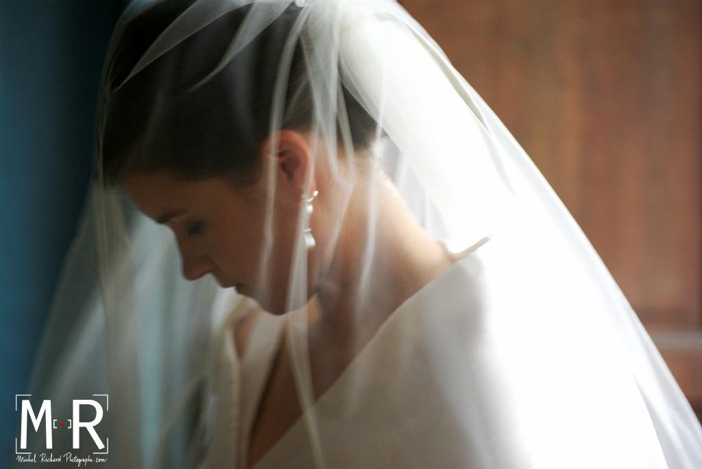 la mariée est en contrejour sous son voile à l'entrée de l'église pour la cérémonie de mariage