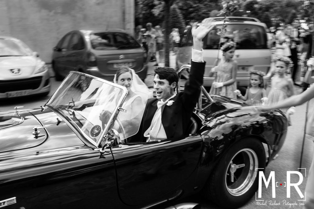les mariés saluent la foule et partent en voiture ford Cobra après la cérémonie de la messe de mariage.
