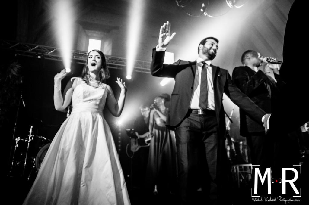les mariés dansent sur scène sous les projecteurs en noir et blanc.