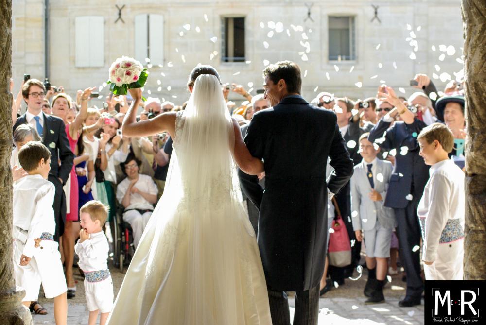 les mariés de dos à la sortie de l'église pour leur cérémonie de mariage, après la messe, sous la pluie de pe pétales de roses