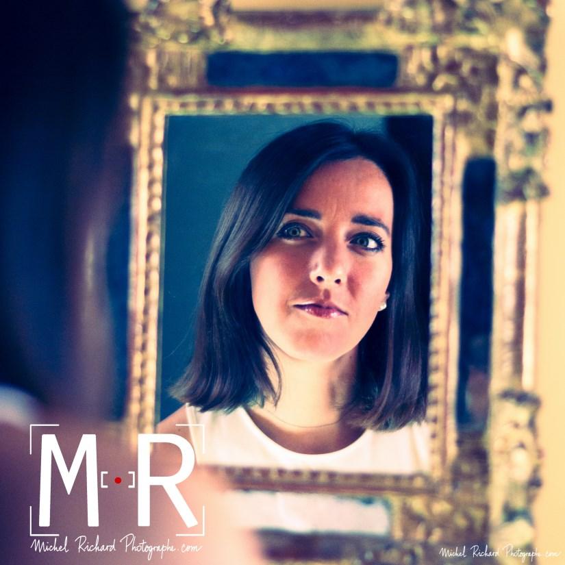 une jeune femme se contemple dans un miroir ancien