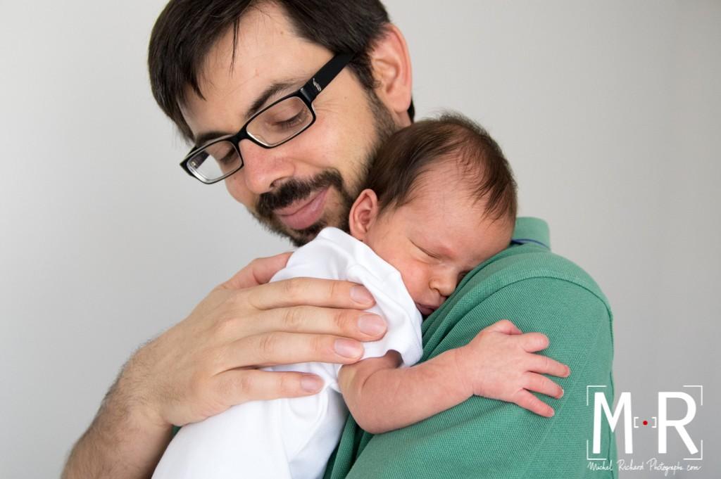 le nouveau fait un calin et dort dans les bras de son père. papa sourit.