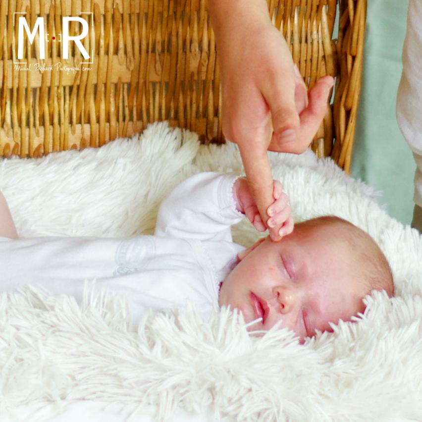 bébé à moitié endormit serre le doigt de maman avec sa main.