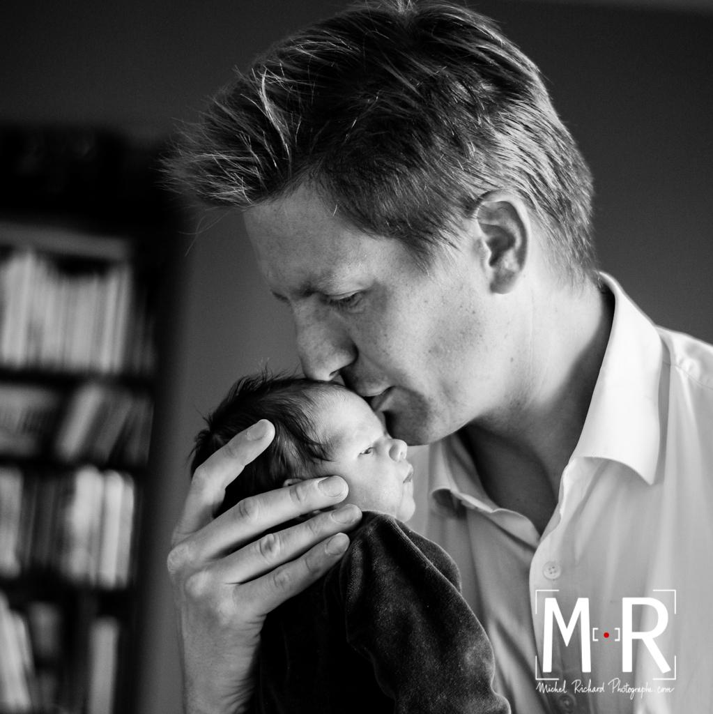 papa fait un baiser sur le front du nouveau né. noir et blanc.