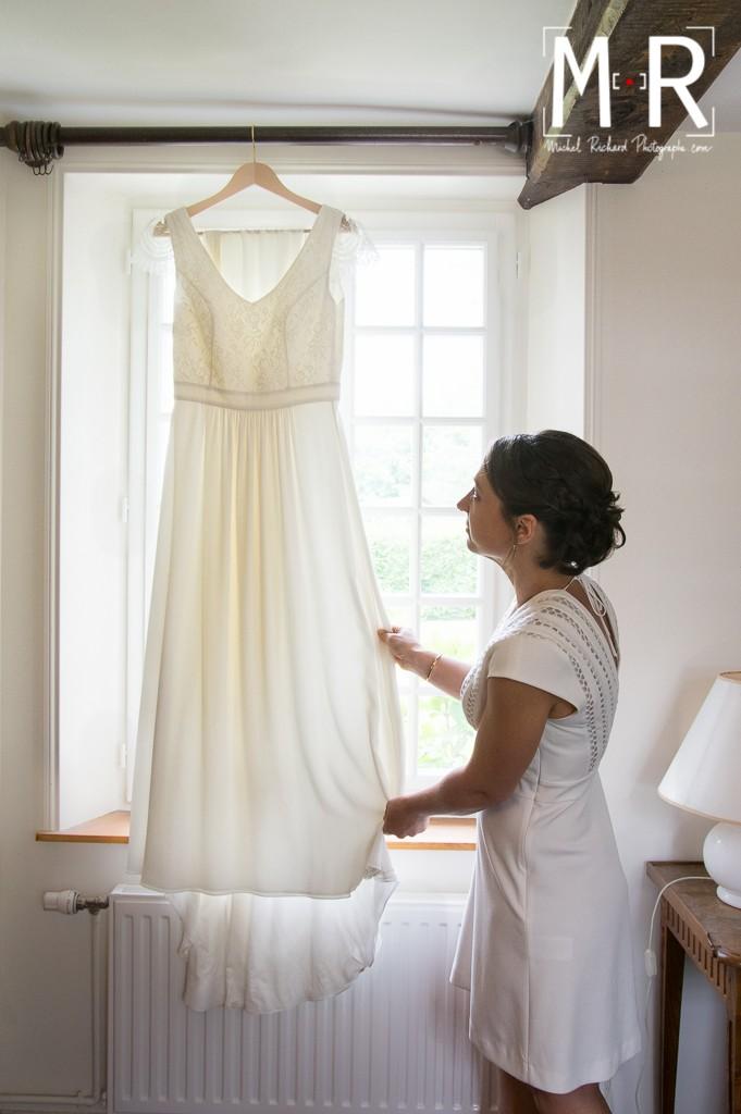 la mariée regarde sa robe à la fenêtre