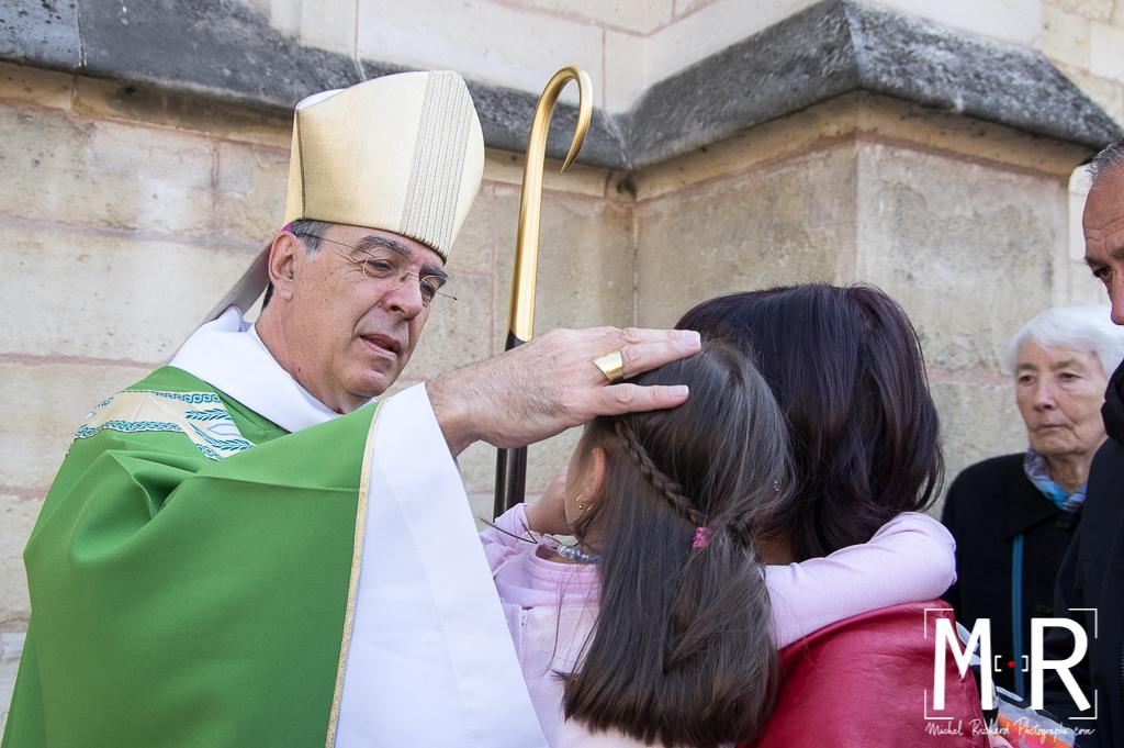 l'évêque bénit un enfant dans les bras de sa mère