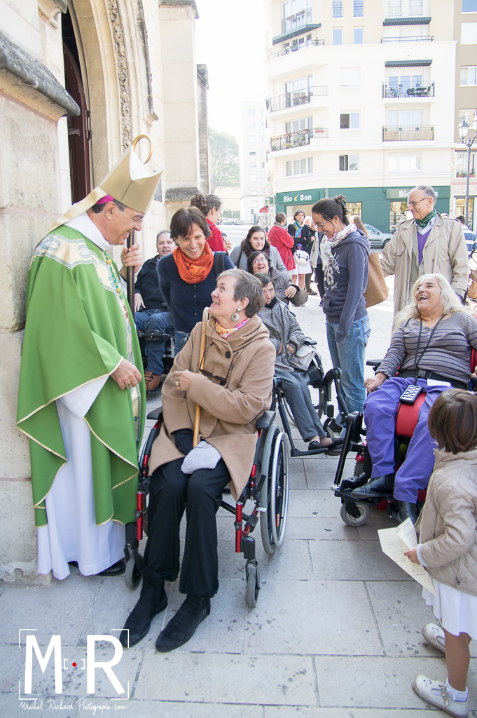 l'évêque rit avec des personnes handicapées en fauteuil roulant