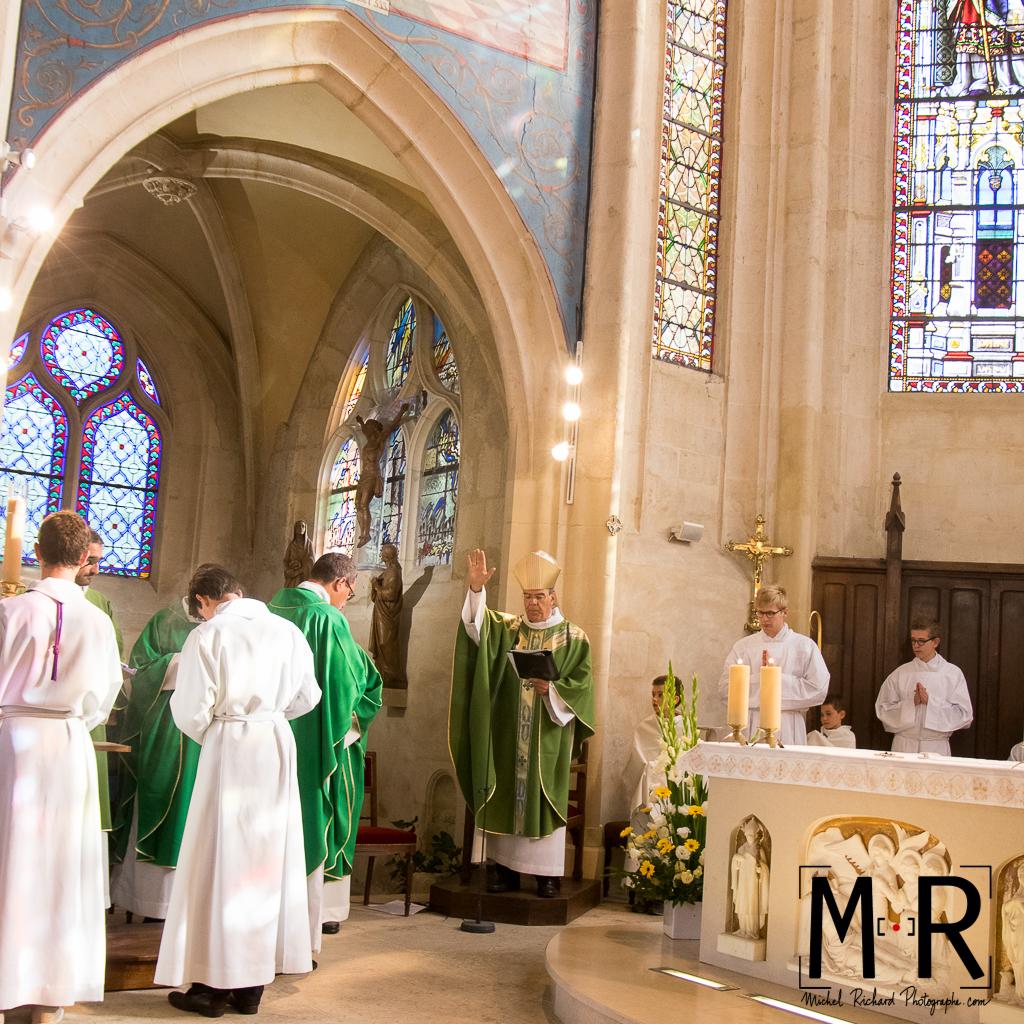 l'évêque bénit le nouveau curé