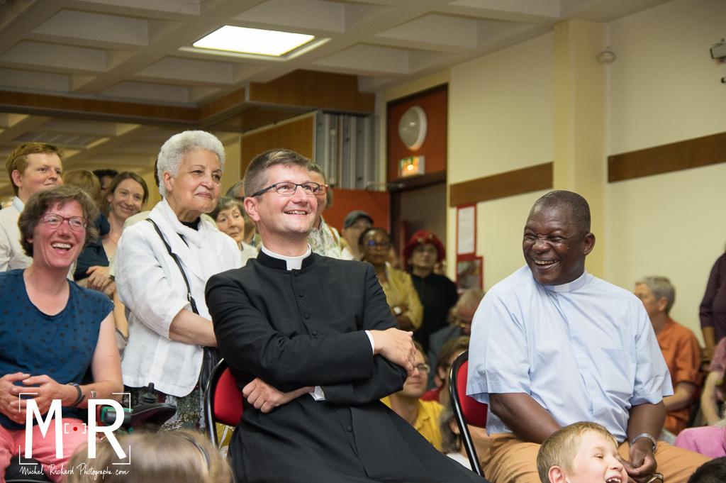 Deux prêtres rient pendant un discours - fête de paroisse