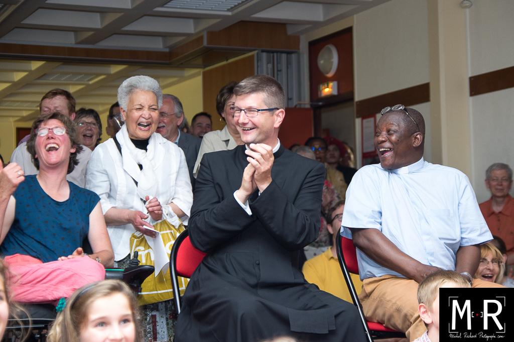 Deux prêtres et les paroissiens rient pendant un discours - fête de paroisse
