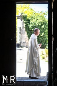 un prêtre sur le seuil de son église
