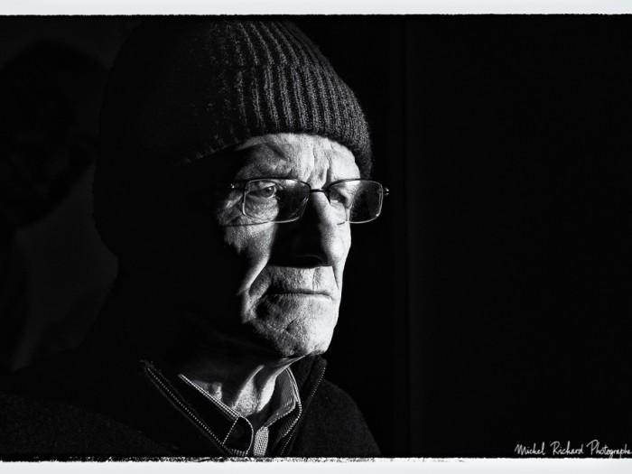 portrait d'homme au bonnet au visage buriné en clair-obscur noir et blanc - portrait au flash par le photographe de portrait à Paris Michel Richard