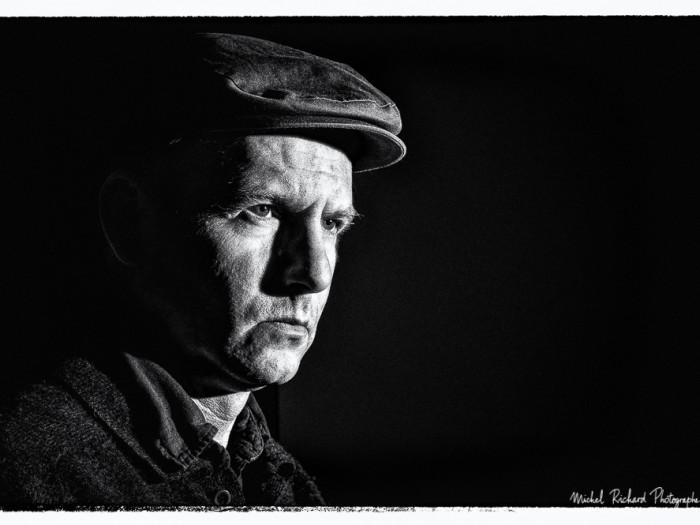 portrait d'homme à casquette au visage clair obscur buriné en - portrait au flash en noir et blanc par le photographe de portrait à Paris Michel Richard